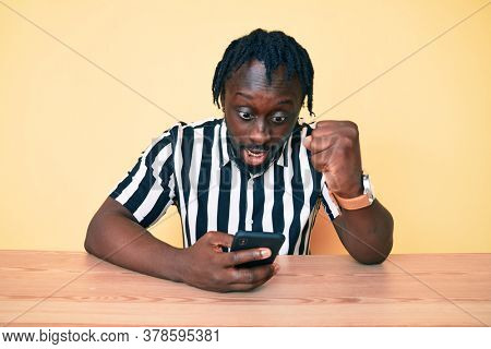 Young african american man with braids using smartphone sitting on the table annoyed and frustrated shouting with anger, yelling crazy with anger and hand raised