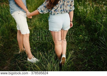 Rear View Of A Romantic Man And Woman Stand On Walk On Field Grass. Concept Of Lovely Family Holding