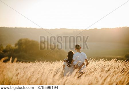 Young Couple Hugging And Looking Away In Autumn At An Outdoor On Park On The Background Field, Grass