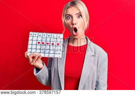Beautiful blonde woman controlling menstruation holding period calendar over red background scared and amazed with open mouth for surprise, disbelief face