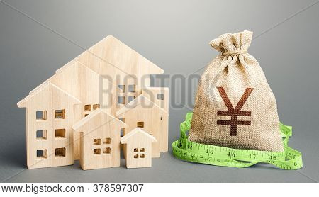 Residential Houses And A Yen Yuan Money Bag. Buying, Fair Price. City Municipal Budget. Property Rea