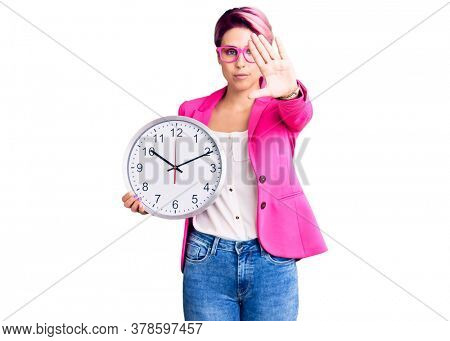 Young beautiful woman with pink hair wearing business jacket and holding clock with open hand doing stop sign with serious and confident expression, defense gesture