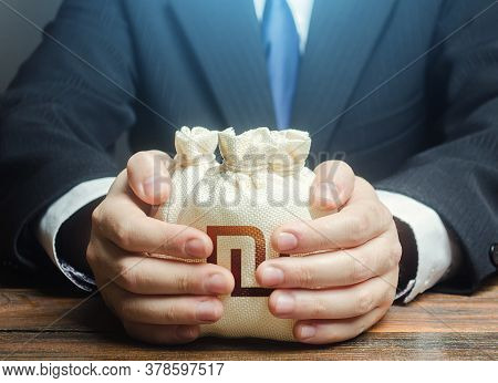 Businessman Covers With Hands Israeli Shekel Money Bags. Corrupt Schemes. Profit Collection And Tax