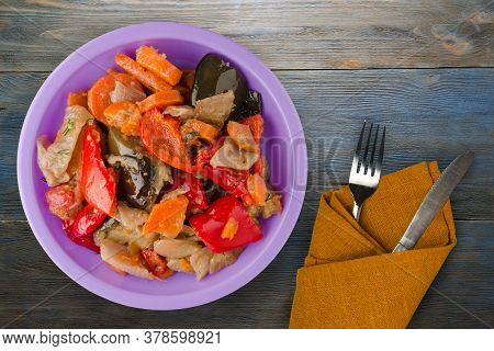 Vegetable Stew On Blue Grey Wooden Background. Stew In Bulgarian On Purple Plate With Fork And Knife