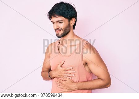 Handsome hispanic man wearing casual clothes with hand on stomach because indigestion, painful illness feeling unwell. ache concept.