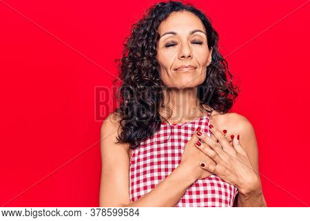Middle age beautiful woman wearing casual sleeveless t shirt smiling with hands on chest, eyes closed with grateful gesture on face. health concept.