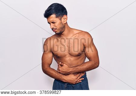 Young latin man standing shirtless with hand on stomach because nausea, painful disease feeling unwell. ache concept.