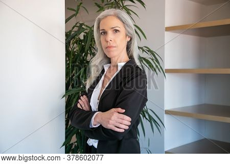 Content Caucasian Businesswoman Standing With Folded Hands. Portrait Of Confident Adult Beautiful Fe