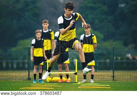 Young Footballer On Training Jumping Over Obstacles. Summer Soccer Camp. Players In A Team Practicin