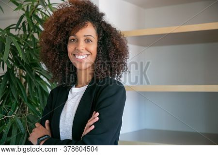 African American Curly Businesswoman Standing With Folded Hands. Portrait Of Successful Confident Yo