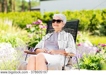 old age, retirement and people concept - happy senior woman with earphones listening to music at summer garden