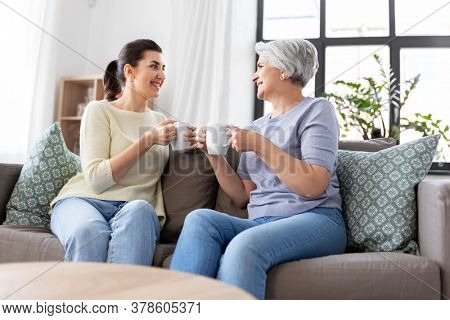 family, generation and people concept - happy smiling senior mother with adult daughter drinking coffee or tea and talking at home