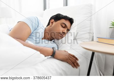 people, bedtime and rest concept - indian man sleeping in bed at home