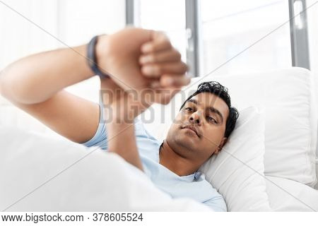 people, bedtime and rest concept - indian man looking at health tracker in bed at home