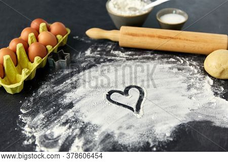 cooking food, culinary and recipe concept - heart shaped doodle on flour, rolling pin, eggs and dough on table