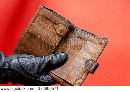 Hand In Black Leather Glove Holds Out Empty Brown Wallet. Male Hand Holds Stolen Wallet With No Mone
