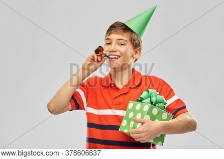 holiday, birthday present and people concept - portrait of happy smiling boy in party hat with gift box and blower over grey background