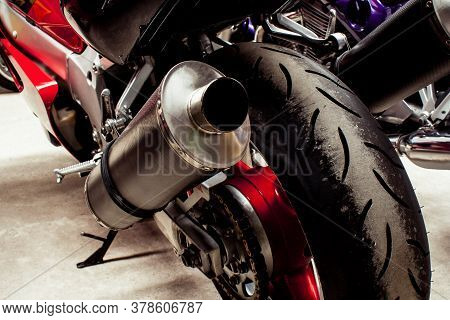 The Back Of Sports Bike Close-up In Garage. Wheel, Brake Disc, Exhaust Pipe, Transmission, Shock Abs