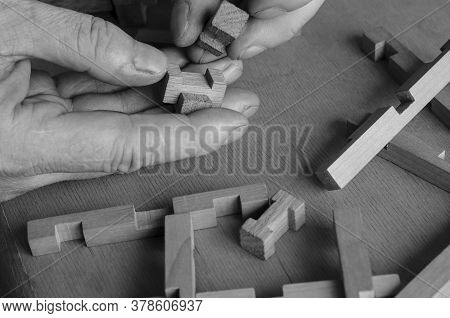 Mans Hands Collect The Details Of The Childrens Wooden Constructor. Close-up Of A Developing Childre