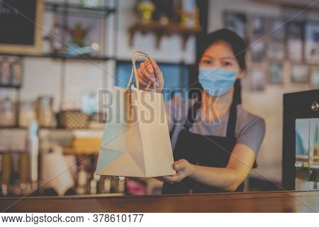 Waitress With Medical Mask Giving Eco Friendly Paper Bag With Take Away Food In Cafe.