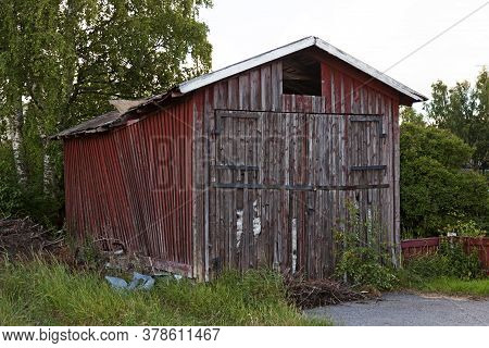 An Old Red Wooden Shed That Is Falling Apart