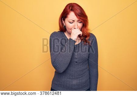 Young beautiful redhead woman wearing casual sweater standing over yellow background feeling unwell and coughing as symptom for cold or bronchitis. Health care concept.