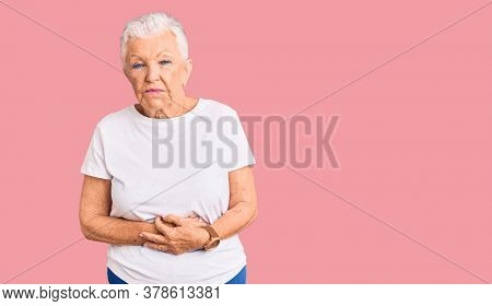 Senior beautiful woman with blue eyes and grey hair wearing casual white tshirt with hand on stomach because indigestion, painful illness feeling unwell. ache concept.