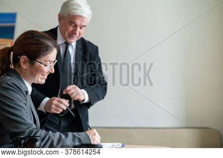 A Woman In A Suit Signs Documents Under The Direction Of A Mature Male Boss. Friendly Colleagues Tal