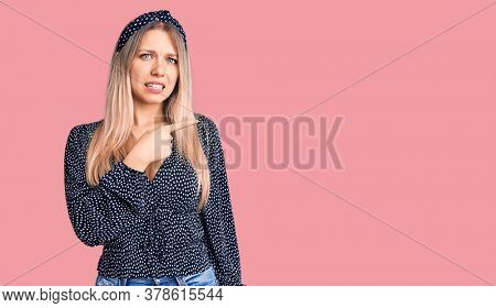 Young beautiful blonde woman wearing casual clothes pointing aside worried and nervous with forefinger, concerned and surprised expression
