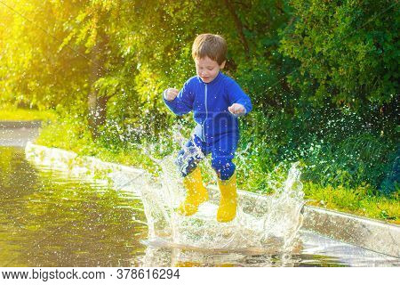 A Happy Boy In Rubber Boots Jumps In Puddles. The Boy Jumps In A Puddle . Bad Weather. Puddles After
