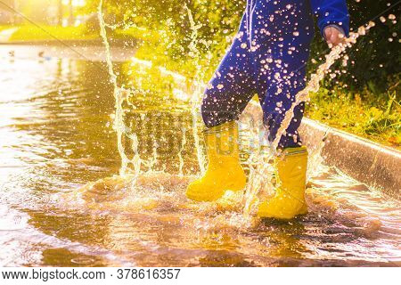 My Rubber-booted Feet Are Bouncing In A Puddle. Article About Rubber Boots. Childrens Summer Shoes.