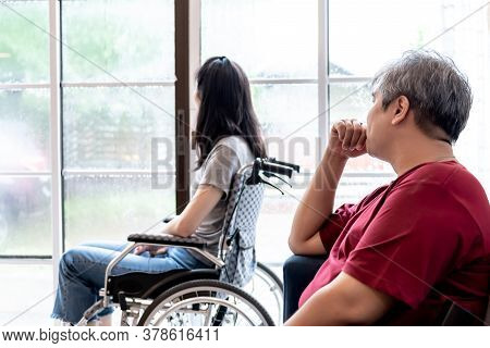 Asian Fat Husband Looking At Wife Which Sick And Sitting In A Wheelchair And She Is Depressed, To He