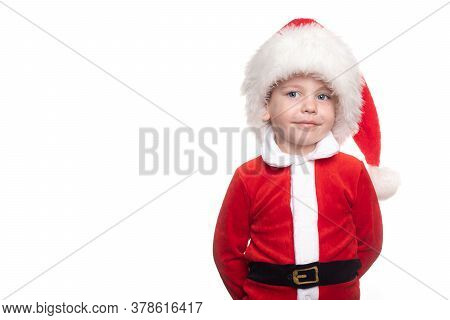 A Boy In A Santa Suit On A White Background Looks Into The Frame . Cute Little Santa. Santa And Plac