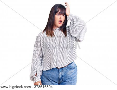 Young plus size woman wearing casual clothes surprised with hand on head for mistake, remember error. forgot, bad memory concept.