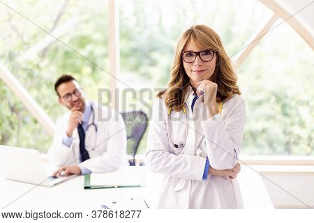Portrait Shot Of Confident Female Doctor Standing In Doctor's Office While Looking At Camera Ands Sm