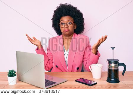 Young african american woman working at desk using computer laptop clueless and confused with open arms, no idea and doubtful face.