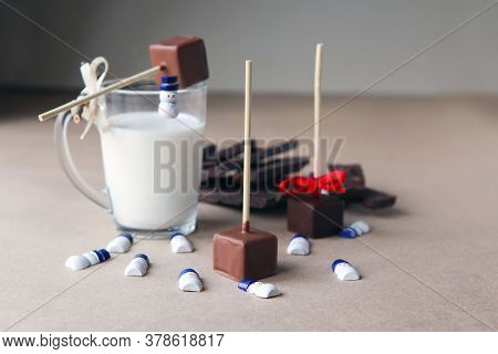 Small Snowmans Near Chocolate Cubes On A Stick With Milk Cup And Aromatic Cocoa And Chocolate On Bro