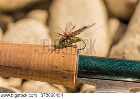 A Macro Shot Of An Artificial Cicada Dry Fly For Fishing For Trout, Positioned On The Cork Handle Of