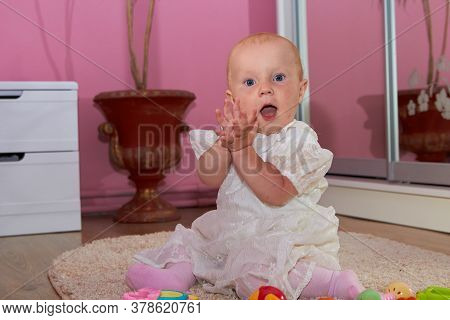 Baby Claps His Hands, Cheerful Baby Sitting On The Carpet And Clapping In His Palm