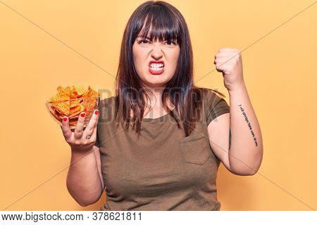 Young plus size woman holding nachos potato chips annoyed and frustrated shouting with anger, yelling crazy with anger and hand raised