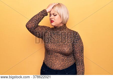 Young beautiful blonde plus size woman wearing casual t-shirt over isolated yellow background surprised with hand on head for mistake, remember error. Forgot, bad memory concept.