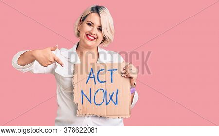 Young blonde plus size woman holding act now cardboard banner smiling happy pointing with hand and finger
