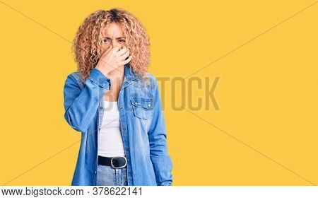 Young blonde woman with curly hair wearing casual denim jacket smelling something stinky and disgusting, intolerable smell, holding breath with fingers on nose. bad smell