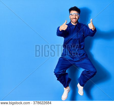 Young handsome hispanic man wearing painter uniform and glasses smiling happy. Jumping with smile on face doing ok sign with thums up over isolated blue background