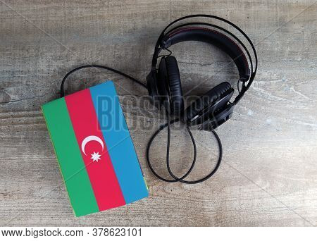 Headphones And Book. The Book Has A Cover In The Form Of Azerbaijan Flag. Concept Audiobooks. Learni