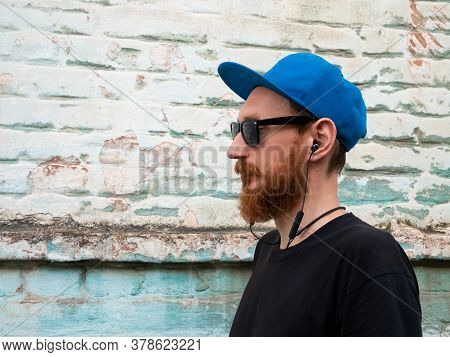 Portrait Of Young Red Bearded Man In Black T-shirt And Snapback In Rock Style On Urban Background Li