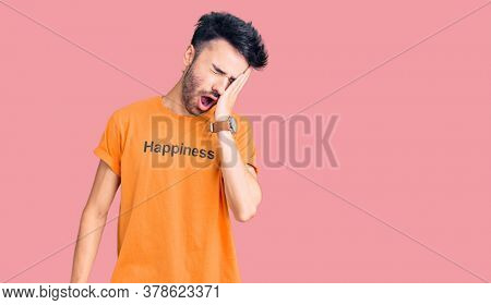 Young hispanic man wearing t shirt with happiness word message yawning tired covering half face, eye and mouth with hand. face hurts in pain.
