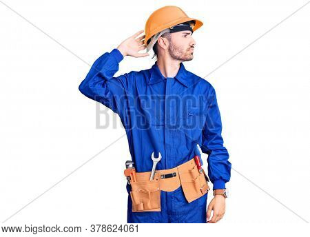 Young hispanic man wearing worker uniform confuse and wondering about question. uncertain with doubt, thinking with hand on head. pensive concept.