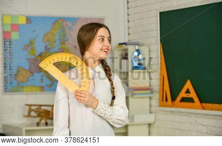 Cute Little Schoolgirl With Geometrical Tool For Mathematics. Elementary School Mathematics Or Maths