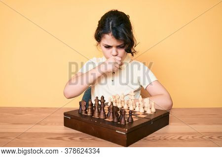 Cute hispanic child playing chess sitting on the table feeling unwell and coughing as symptom for cold or bronchitis. health care concept.